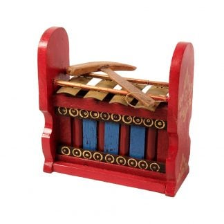 This is a product image of the Gamelan - Budget - Small 4 key. The instrument has four gold keys suspended by bamboo and wire. The casing is mainly red with some blue, gold and black decoration. A beater is laying on top of the instrument. The image has been taken from the front and the instrument is facing slightly to the left.