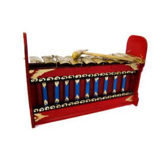 This is a product image of the Gamelan (Gangsa Pemad?) - Budget - Medium 10 key. The image has been taken from the front and the instrument is facing slightly to the right. It is red and blue with gold keys suspended by wire, and the beater is lying on top of the keys.