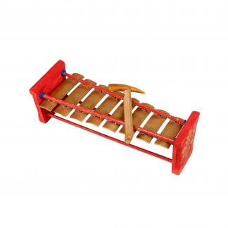 This is a product image of the Gamelan (Metallophone) - C major from a higher angle. It is largely red in colour with eight metal bars suspended across two bamboo struts.