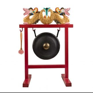 This is a product image of the Gong Set - 12in (30cm) diameter Gong with Stand and Beater. The frame is a sleek metal design, painted red with a two ornate wooden dragons in red white and gold, sitting on the crossbar. The Gong is matt black with a gold boss and is hanging evenly from two hooks. The beater is attached to a hook on the left hand side of the stand. The entire stand is facing slightly to the left.