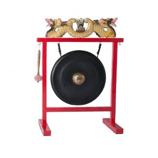 This is a product image of the Gong Set - 16in (40cm) diameter Gong with Stand and Beater. The stand is made of sturdy metal bars, spray painted red. Across the top are two dragons facing away from each other, ornately coloured. The gong is hanging down inside the frame from two hooks, and the beater is hanging on a hook on the left hand side of the instrument.