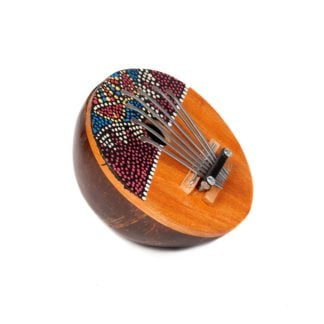 This is a product image of the Thumb Piano (Mbira) - coconut, painted. It is a smoothed and polished half coconut shell with metal prongs in the centre, situated on a bridge. The top half of the shell on the flat side has been painted with dots which form a coherent pattern. The instrument is partially upright and facing to the right.