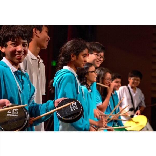 Action shot of students playing Tamborim and Surdo in Nexus School, Malaysia